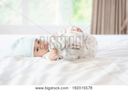 Portrait of 4 month Asian baby lying and playing foot on white bed in bedroom at house.
