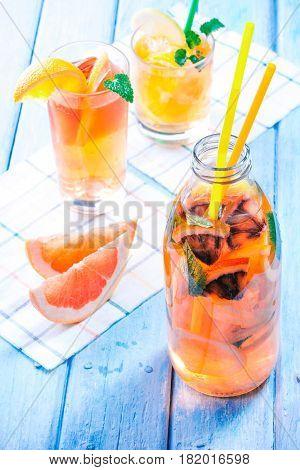 Detox water with various citrus fruit. Glass bottle with slices of orange, blood orange, lemon and grapefruit. Blue plank background