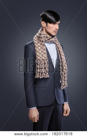 Handsome young man in black classic suit and white shirt with a wool scarf. Confident businessman on dark background.