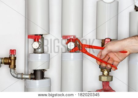 repair man is fixing a valve in a heating room