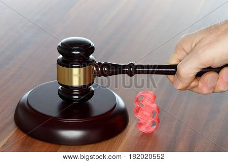 gavel in hand and red paragraph symbol on desk