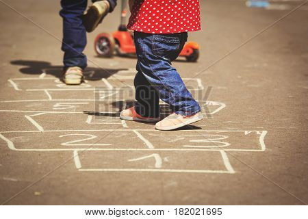 kids playing hopscotch on playground outdoors, active kids