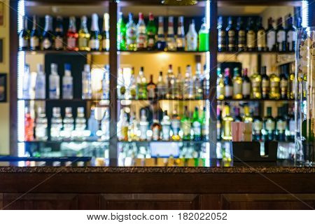 Close up empty counter of modern bar with drinks blurred