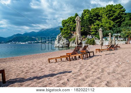 Sun loungers and umbrellas are on the beach