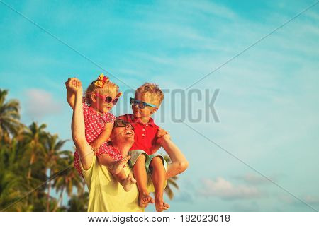 happy father with two kids on shoulders play at sky