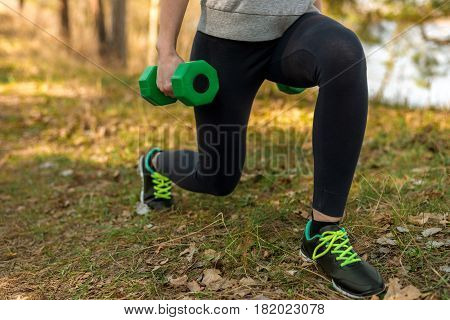 Girl in sports pants and hoodie crouching with green dumbbells