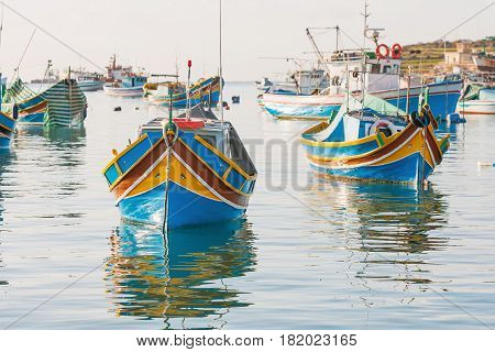 Mediterranean traditional colorful boats luzzu. Fisherman village in the south east of Malta. Early winter morning in Marsaxlokk Malta.