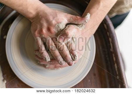 Hands working on pottery wheel crafting bowl