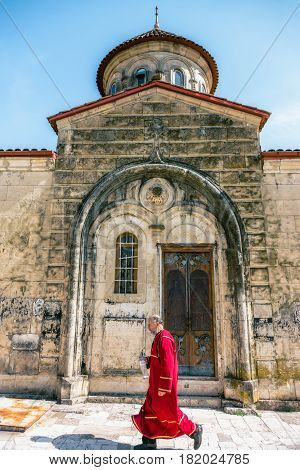 Georgia, Kutaisi - April 01, 2017: Monk in Motsameta monastery. The Tsar Bagrat III reconstructed the church in the 10 th century. The building was reconstructed again in the 19 th century.
