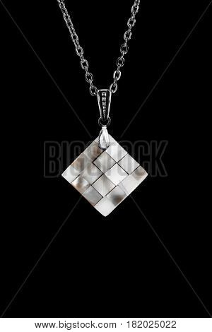 Nacre chess pendant on a chain isolated over black