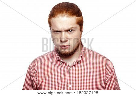 doubting confused bearded readhead businessman with red shirt and freckles looking at camera. studio shot isolated on white.