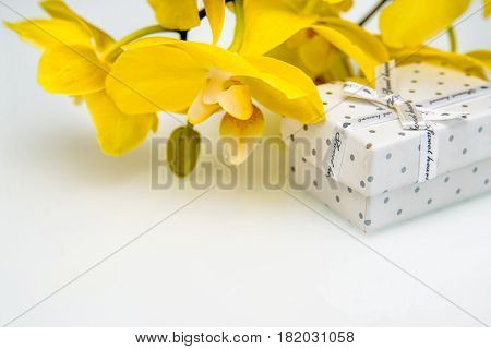 Gift box on a background of yellow orchids