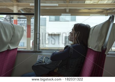 tried and sleep asian lady on seat in train in Japan