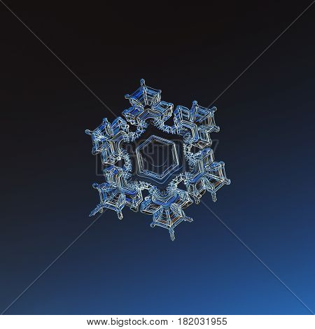 Macro photo of real snowflake: medium size snow crystal of star plate type with short, sharp arms and big, flat central hexagon. Snowflake glittering on dark blue gradient background in cold light.