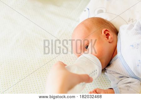 Mother feeding her baby with a milk bottle.