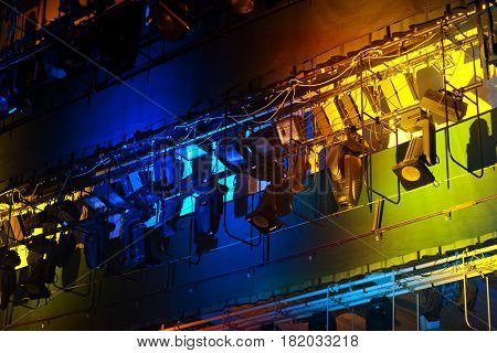 Professional stage spotlight lamps rack on color background