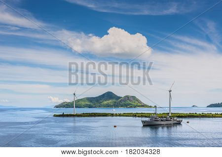 Victoria Mahe island Seychelles - December 17 2015: View to the island St. Anne. Wind turbines and hydrographic survey ship INS Darshak J21 in the foreground in Victoria harbor Mahe Seychelles.