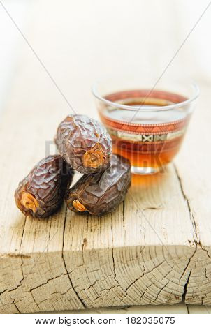 Few ripen dates and arabic coffee served in a traditional cup. Rustic food photography set up.
