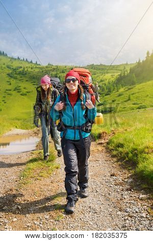 happy woman hiker with backpack trekking on trail in mountains. Girl tourist walking on dirt road in forest. Healthy lifestyle adventure, camping on hiking trip
