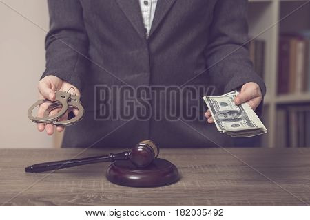 Detail of corrupted judge balancing the scale before making a verdict holding handcuffs in one and bribe money in the other hand. Selective focus
