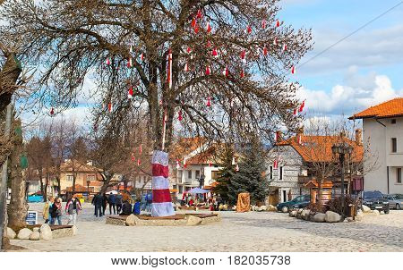 Bansko, Bulgaria - February 26, 2015: Many Bulgarian traditional spring sign Martenitsa on the tree and people walking in town center