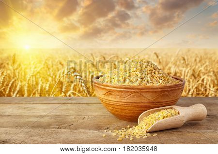 bulgur or couscous grains in bowl on table with ripe field on the background. Agriculture and harvest concept. Golden wheat field on sunset. Healthy eating for diet and vegan