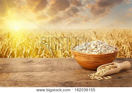 uncooked oat flakes in bowl on table with ripe cereal field on the background. Golden field on sunset. Uncooked porridge. Agriculture and harvest concept. Healthy eating for diet and vegan