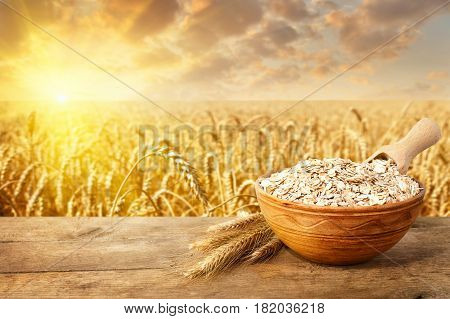 uncooked oatmeal in bowl on table with ripe cereal field on the background. Golden field on sunset. Uncooked porridge. Agriculture and harvest concept. Healthy eating for diet and vegan