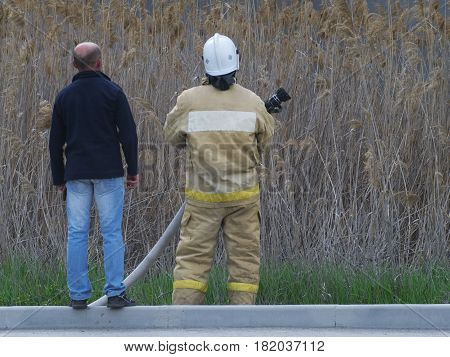 The fireman and the man are looking somewhere