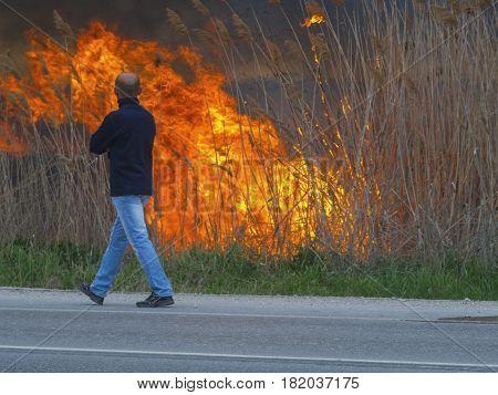 A man is walking along the road near a fire