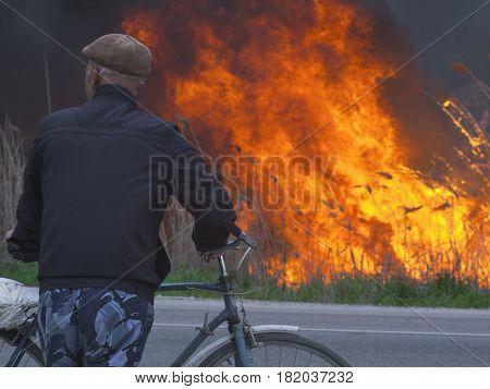 A cyclist looks at a fire near a road