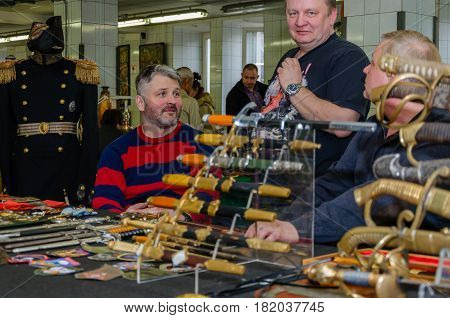 Moscow, Russia - March 19, 2017: Sellers of antique swords and daggers are waiting for buyers-collectors at the fair