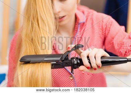 Woman Wearing Pajamas Curling Her Hair