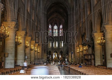 Paris France - July 3 2015: People visiting the interior of Notre Dame in Paris France showing high altar