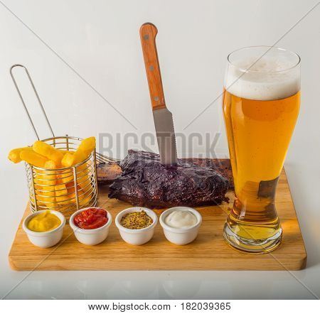 Slow Cooked Oak Smoked Glazed Beef Rib, French Fries, Four Sauces, Beer, Whole On Wooden Board