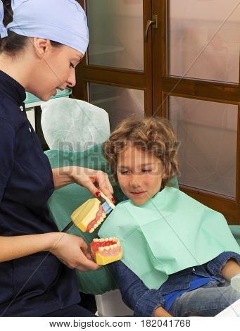 woman dentist explaining brushing procedure to a kid using artificial teeth's in clinic studio.