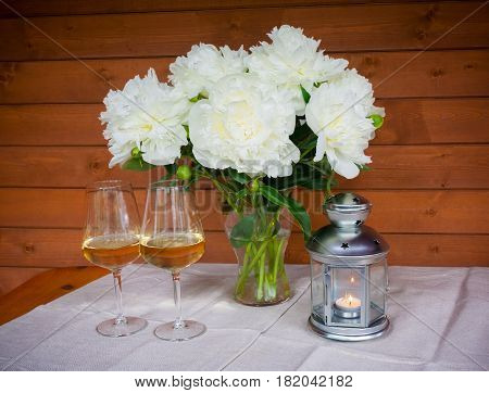 Bouquet of white peonies glasses of wine and lantern