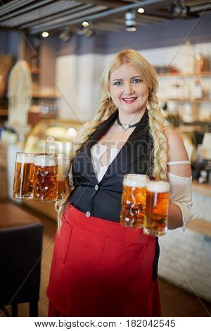 Smiling blonde woman stands near table holding several glass mugs with beer in both hands.