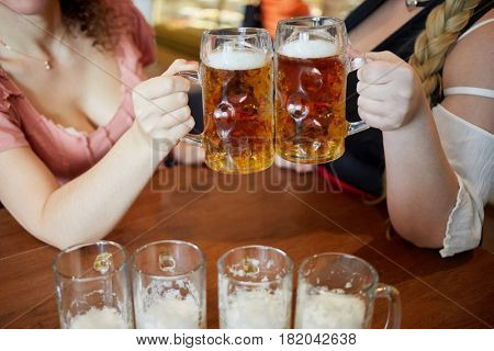 Two women clang glass mugs with beer above table, no faces.