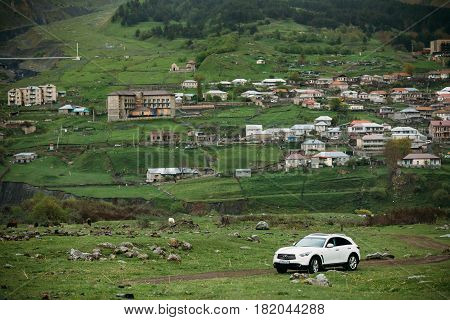 Stepantsminda Gergeti, Georgia - May 23, 2016: White Infiniti FX30d turbo diesel SUV car on country road in summer mountains landscape. The Infiniti is a mid-size luxury crossover SUV produced by Nissan