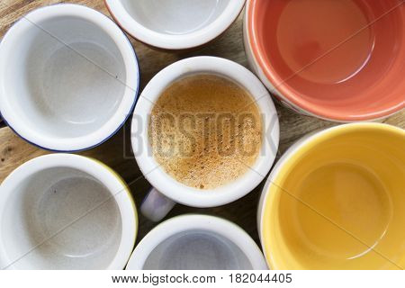 top view of a cup of creamy espresso coffee next to others empty cups