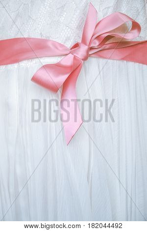 Detail Of A Pink Bow On The White Lace Dress Of A Flower Girl At A Wedding