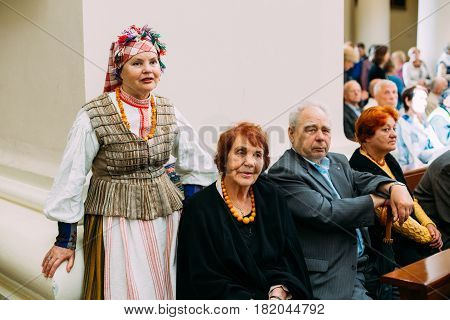 Vilnius, Lithuania - July 6, 2016: Woman dressed in traditional folk costume in Cathedral Basilica of Saints Stanislaus and Vladislaus during celebration of Statehood Day. Holiday in commemorate coronation in 1253 of Mindaugas King