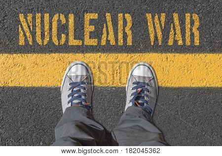NUCLEAR WAR print with sneakers on asphalt road top view.