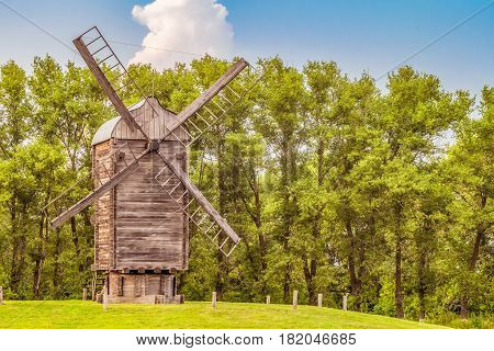 Wooden windmill on a background of green trees. Summer rural landscape.