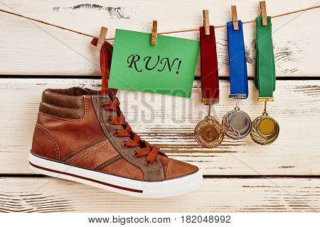 Sneaker, motivation card and awards. Sport as an adventure.
