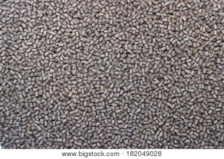 A background Image of dark brown granulated animal feed.