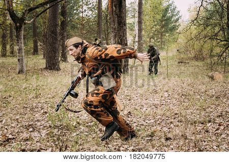 Pribor, Belarus - April 24, 2016: Re-enactor Dressed As Soviet Russian Red Army Soldier Of World War II Running Under Bullets From Shooting German Soldier At Historical Reconstruction In Forest