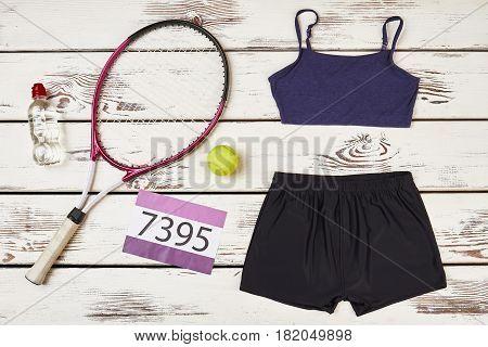 Badminton racket and women's sportswear. Perseverance leads to achievements.
