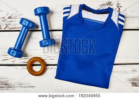 Male T-shirt, dumbbells and espander. How to relieve stress.